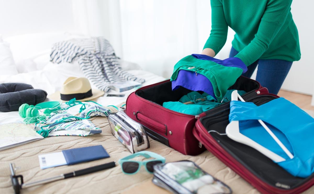 женщина укладывает вещи в чемодан